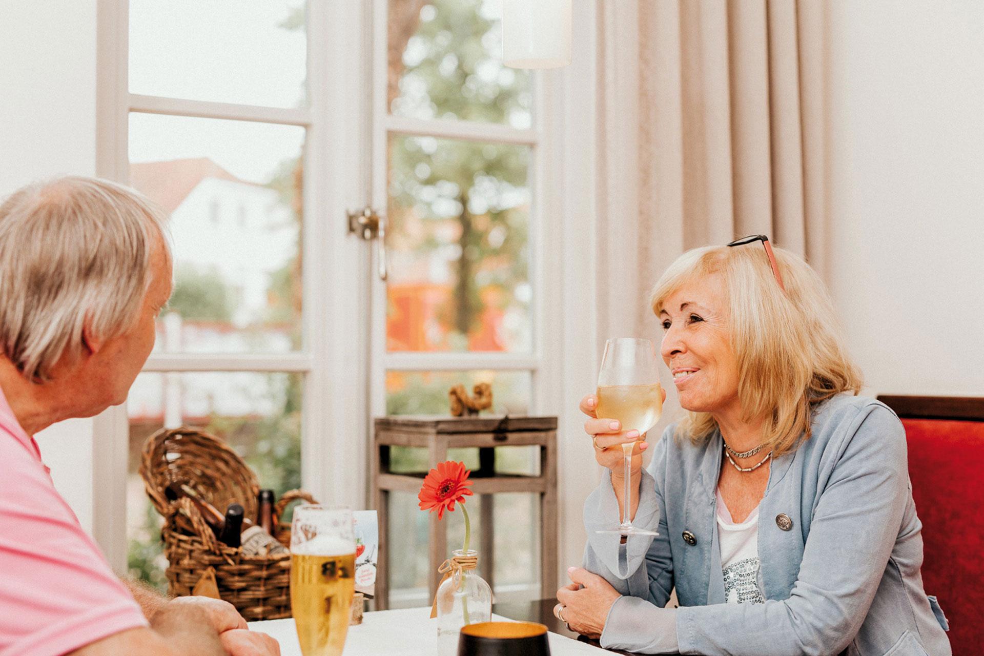 Frau trinkt Weißwein in Restaurant